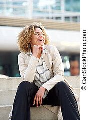 young african american woman sitting on steps in city and laughing