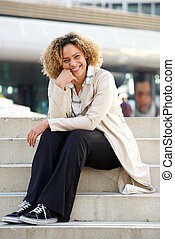 young african american woman sitting on steps in city