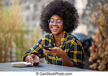 young african American woman sitting outside looking at mobile phone and laughing