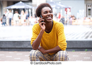 young african american woman sitting outside talking on cellphone
