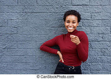 young african american woman smiling and pointing finger
