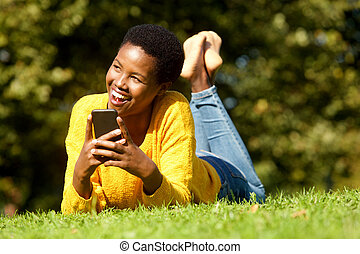 young african american woman smiling in park with cellphone