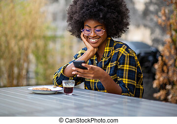 young african American woman smiling outside looking at mobile phone