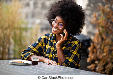 young african American woman smiling outside talking with mobile phone
