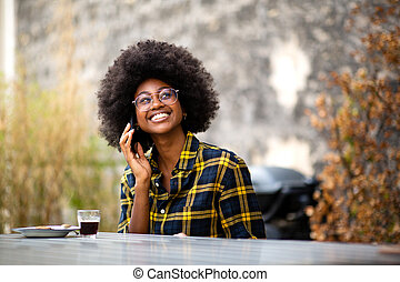 young african American woman smiling outside talking with phone