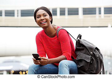 young african american woman smiling with cellphone and bag in the city