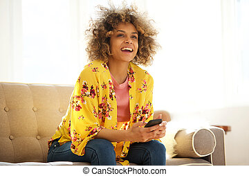 young african american woman smiling with cellphone at home