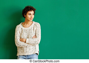 young african american woman standing against green background with arms crossed