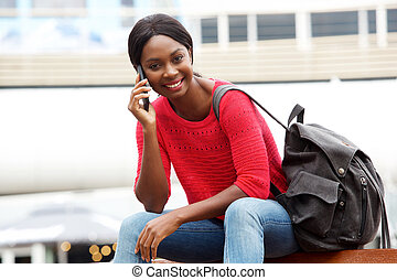 young african american woman talking on cellphone while sitting down in the city with bag