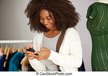 young african american woman using cell phone in clothing store