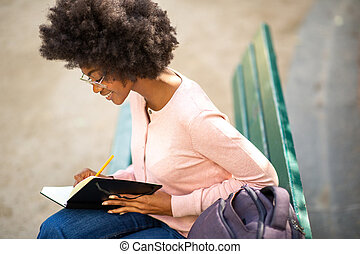 young african american woman with glasses writing in book