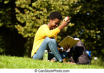 young african american woman witting in park reading book