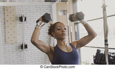 Portrait of young african athlete doing dumbbell exercises in modern gym.