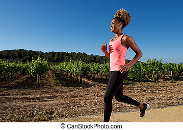 young african female in sportswear running outdoors