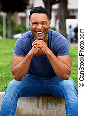african man sitting outdoors and laughing