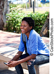 young african woman laughing outside with cell phone