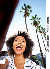 Portrait of young african woman laughing outside with curly hair