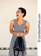 young african woman laughing with striped dress and bag