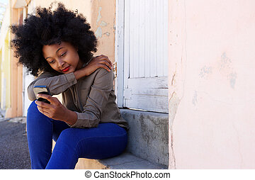 young african woman sitting on steps with mobile phone