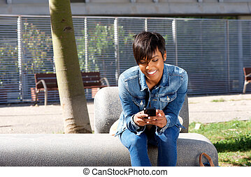young african woman sitting outside and using mobile phone
