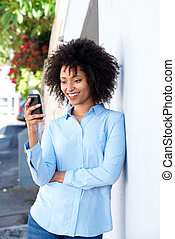 young african woman standing by a wall outdoors using smart phone