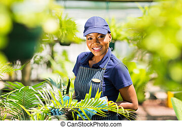 young afro american nursery worker gardening