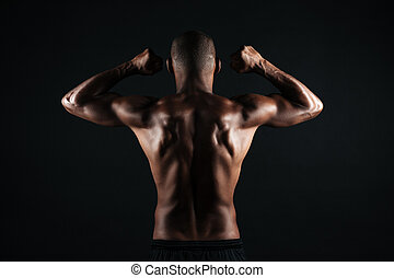 Portrait of young afro american sports man, standing back, showing musculs