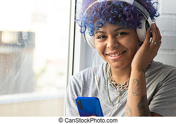 portrait of young afro american woman with mobile phone and headphones at the window
