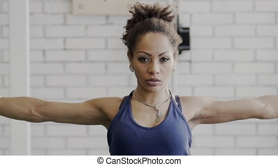Portrait of young afroamerican lady who is doing warm up exercises in the gym before training.