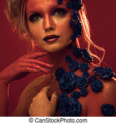 Portrait of young and attractive woman with art makeup. Fiery colors, glitter on face and floral decoration