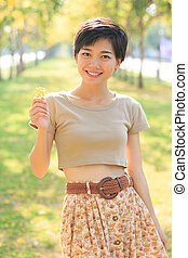 portrait of young and beautiful asian woman standing in park wit