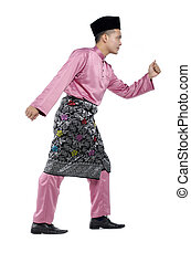 Portrait of young and handsome asian man with traditional clothing during hari raya over white background