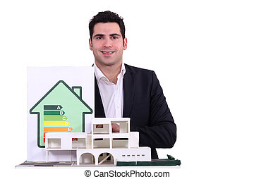 portrait of young architect posing near model and house with energy rating