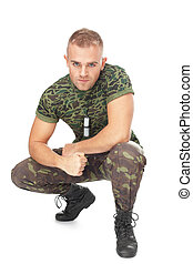 Portrait of young army soldier squatting isolated on white...