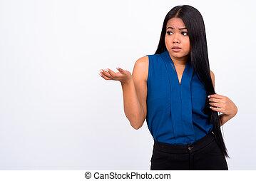 Portrait of young Asian businesswoman shrugging shoulders