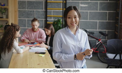 Portrait of young asian female entrepreneur holding digital tablet looks at camera and smiling on busy start-up office background