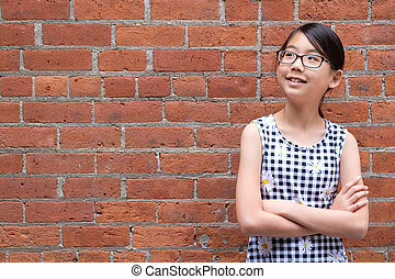 Portrait of young Asian girl against red brick wall