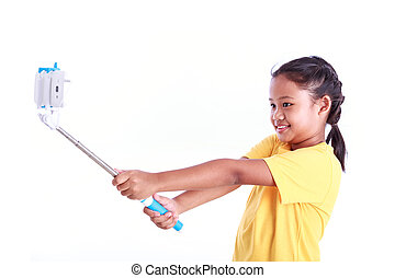Portrait of young Asian girl with selfie stick isolated on...