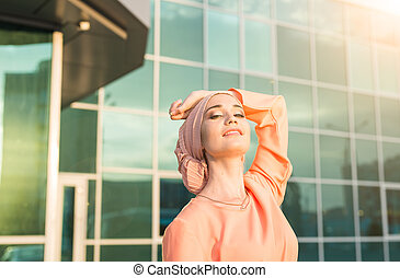 Portrait of young asian muslim woman in head scarf smile outdoor