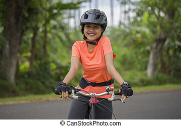 portrait of young asian woman cyclist with bike