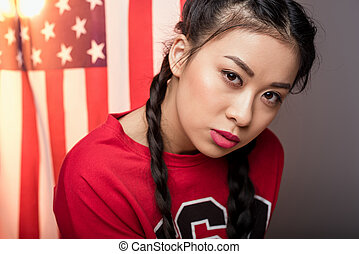 portrait of young asian woman posing in front of USA flag, Independence Day of America