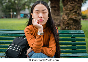 Asian woman sitting on a bench in the park