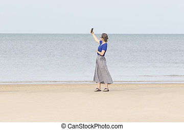 portrait of young asian woman taking selfie photography on sea beach