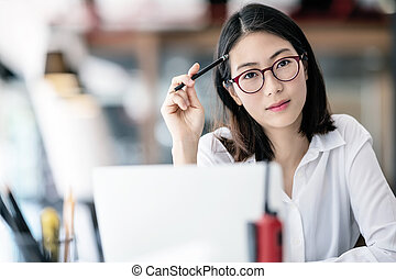 Portrait of young asian woman with glasses holding pencil and looking camera while sitting at her office desk