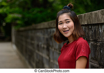 Portrait of young Asian woman with short hair outdoors