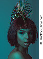 portrait of young astonished african american woman in stylish headpiece