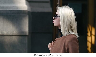 Portrait of young attractive blonde woman in autumn city. Girl have stylish look, sunglasses and nose piercing. Lady walking on the street alone. Fashion and beauty concept