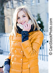 portrait of young attractive blonde woman in winter in the yellow jacket scarf happy smiling & looking at camera outdoor