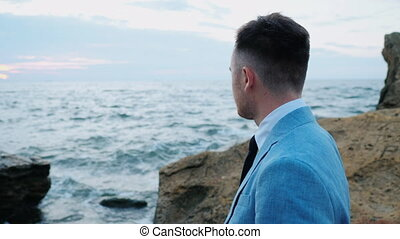 Portrait of young attractive business man or groom stands on sea shore with rocks and watching beautiful sunset or sunrise alone. 4k. Slow motion.