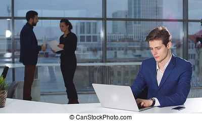 Portrait of young attractive businessman working at a desk, use laptop in the office.